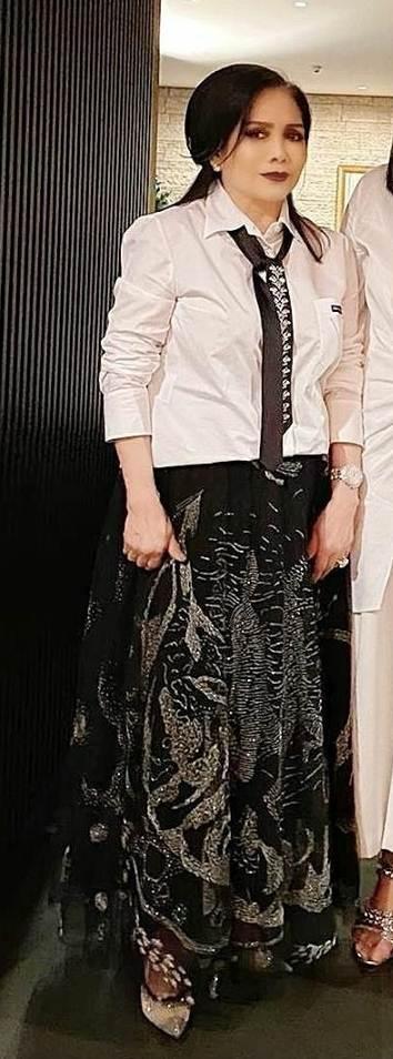มิกซ์แอนด์แมตช์ความเท่กับความวิบวับด้วยเสื้อเชิ้ตสีขาว ผูกโบเป็นไท และกระโปรงยาวปักลวดลายสวยงาม