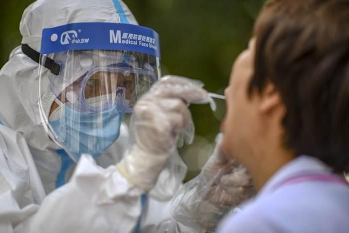 เจ้าหน้าที่แพทย์เก็บตัวอย่างที่เขตเทียนซาน ในอุรุมชี เมืองเอกของเขตปกครองตนเองซินเจียงอุยกูร์ ทางตะวันตกเฉียงเหนือของจีน เมื่อวันที่ 20 ก.ค. 2020--แฟ้มภาพซินหัว
