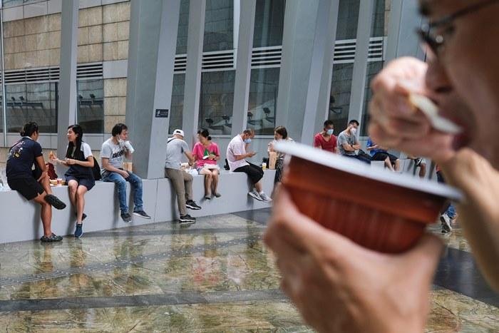 ผู้คนกินอาหารตามมุมต่างๆในห้างสรรพสินค้าในฮ่องกงหลังจากที่รัฐบาลห้ามกินอาหารในร้านหรือศูนย์อาหาร ซึ่งเป็นหนึ่งในมาตรการคุวบคุมโควิด ภาพเมื่อวันที่ 29 ก.ค. (ภาพรอยเตอร์ส)