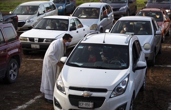นักบวชชาวคริสต์สวมหน้ากากป้องกัน ทักทายต้อนรับสมาชิกโบสต์ซึ่งกำลังนั่งอยู่ในรถยนต์ของพวกเขา  ก่อนเริ่มพิธีมิสซาซึ่งไปจัดกัน ณ โรงภาพยนตร์ไดรฟ์อินแห่งหนึ่งในเม็กซิโก เมื่อวันอาทิตย์ (2 ส.ค.) ทั้งนี้เม็กซิโกเป็นประเทศหนึ่งที่โรคโควิด-19 ยังคงระบาดหนัก