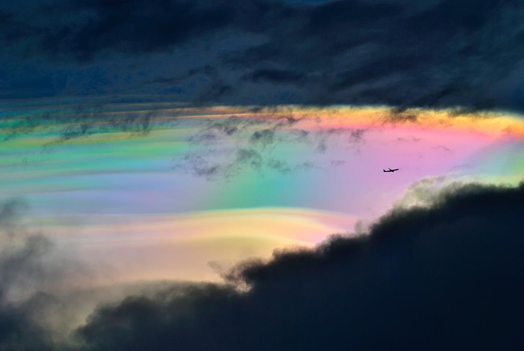 ปรากฏการณ์เมฆสีรุ้ง หรือ irisation เกิดจากการที่แสงอาทิตย์สีขาวตกกระทบเม็ดน้ำขนาดต่างๆ ในเมฆจางๆ ซึ่งเป็นเมฆที่มีจำนวนหยดน้ำไม่หนาแน่นมากนัก เมื่อแสงตกกระทบหยดน้ำแต่ละหยด จะเกิดการหักเหเปลี่ยนทิศทางไปจากแนวเดิม แต่เนื่องจากแสงสีต่างๆ (ที่ประกอบขึ้นเป็นแสงสีขาว) หักเหได้ไม่เท่ากัน ผลก็คือ แสงสีขาวแตกออกเป็นสีรุ้ง และเนื่องจากในเมฆจางๆ ที่ว่านี้มีเม็ดน้ำขนาดต่างๆ กัน ทำให้สีรุ้งสีหนึ่ง ที่หักเหออกจากเม็ดน้ำขนาดหนึ่งๆ ซ้อนทับกับสีรุ้งอีกสีหนึ่ง ที่มาจากเม็ดน้ำอีกขนาดหนึ่ง จึงทำให้มองเห็นสีรุ้งมีลักษณะเหลือบซ้อนทับกันอย่างสลับซับซ้อน (ภาพโดย : รุจิรา สาธิตภัทร / Camera : Nikon D3000 / Focal length : 210 mm. / Aperture : f/7.1 / ISO : 100 / Exposure : 1/800 sec)
