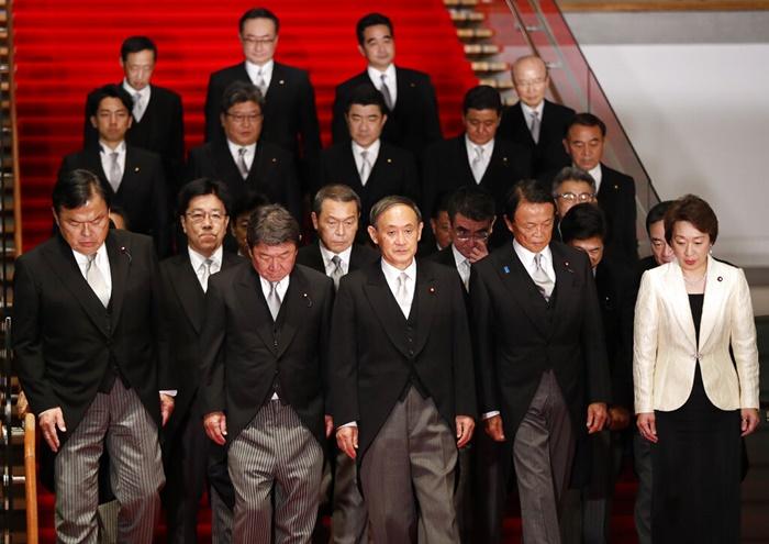 นายกรัฐมนตรีคนใหม่ของญี่ปุ่น โยชิฮิเดะ ซูงะ (กลาง) เดินนำคณะรัฐมนตรีของเขา ขณะเตรียมตัวถ่ายภาพหมู่ ณ ทำเนียบอย่างเป็นทางการของนายกรัฐมนตรี ในกรุงโตเกียว วันพุธ (16 ก.ย.)