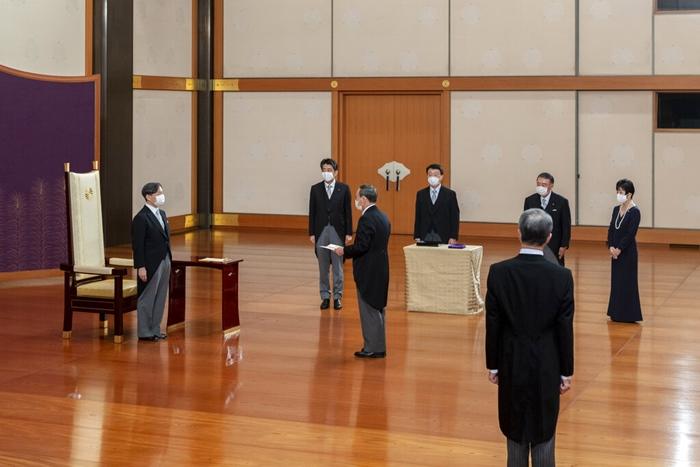สมเด็จพระจักรพรรดินารุฮิโตะ แห่งญี่ปุ่น (ซ้าย) โปรดเกล้าฯให้ โยชิฮิเดะ ซูงะ ว่าที่นายกรัฐมนตรีเข้าเฝ้าฯ โดยที่มีนายกรัฐมนตรีชินโซ อาเบะ (กลางด้านหลัง) มองอยู่ ในพิธีปฏิญาณตนเข้ารับตำแหน่งของซูงะ ณ พระราชวังหลวงในกรุงโตเกียว วันพุธ (16 ก.ย.)