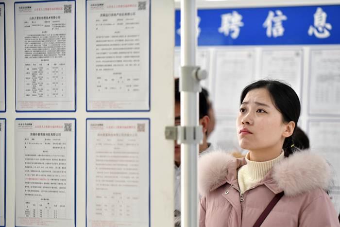 นักศึกษาจีนจบใหม่กำลังอ่านประกาศรับสมัครงานในมหกรรมรับสมัครงานที่เมืองจี่หนัน มณฑลซันตง ภาพ 22 ก.พ. 2019 (แฟ้มภาพซินหัว)