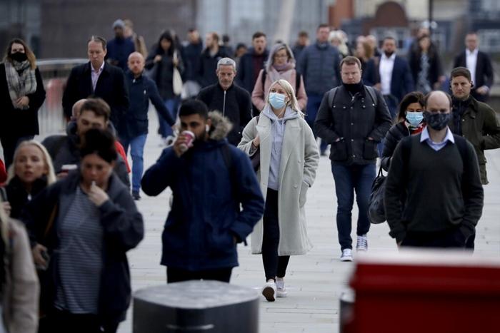 """ผู้เดินทางซึ่งสวมหน้ากากป้องกันกันบางตา เดินข้ามสะพาน """"ลอนดอน บริดจ์"""" ในช่วงชั่วโมงเร่งด่วน มุ่งหน้าไปยังออฟฟิศในย่านการเงิน """"ซิตี้ออฟลอนดอน"""" ในกรุงลอนดอน สหราชอาณาจักร เมื่อวันจันทร์ (12 ต.ค.)"""