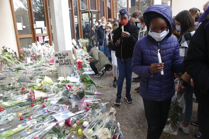 ผู้คนจำนวนมากวางช่อดอกไม้และจุดเทียนไว้อาลัยเมื่อวันเสาร์ (17 ต.ค.) ที่บริเวณด้านนอกของโรงเรียนชานกรุงปารีสซึ่งครูซามูเอล ปะตี ถูกสังหารโหดในวันศุกร์ (16)