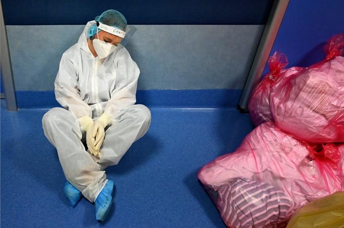 บุคลากรทางการแพทย์ผู้หนึ่งนั่งพักอยู่บนพื้นของหอไอซียูสำหรับผุ้ป่วยโควิด-19 ที่โรงพยาบาลกาซิล ปาลอกโก ใกล้ๆ กรุงโรม ประเทศอิตาลี วันพฤหัสบดี (22 ต.ค.)
