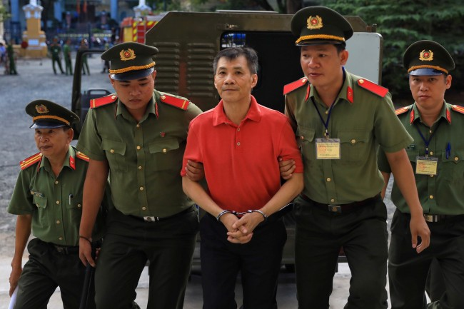 ภาพแฟ้มปี 2562 นายไมเคิล เหวียน ขณะถูกตำรวจเวียดนามควบคุมตัวขึ้นศาลในนครโฮจิมินห์. -- Reuters.
