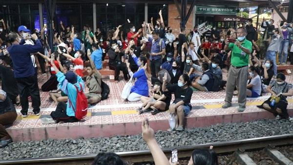 คณะราษฎรอยุธยา ชูสามนิ้วนั่งเคารพเพลงชาติ บนสถานีรถไฟ แสดงจุดยืนต่อต้านการใช้ความรุนแรง