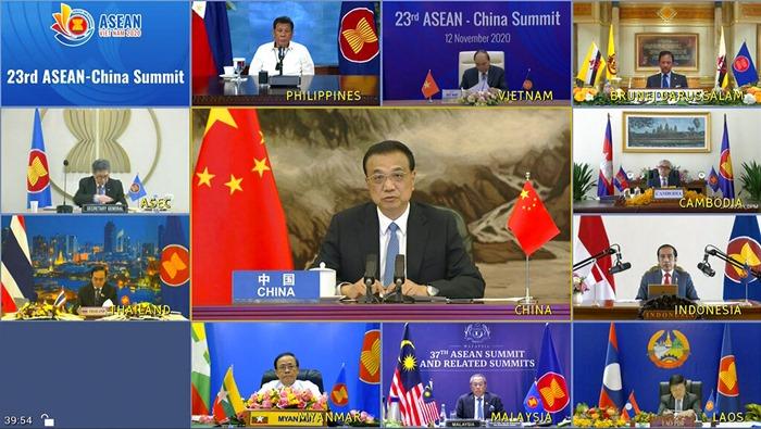 จอภาพแสดงให้เห็นนายกรัฐมนตรี หลี่ เค่อเฉียง ของจีน (กลาง) กำลังพูดระหว่างการประชุมสุดยอดทางออนไลน์กับบรรดาผู้นำชาติอาเซียนในวันพฤหัสบดี (12 พ.ย.)