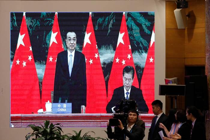 บนจอภาพฉายภาพรัฐมนตรีว่าการพาณิชย์จีน นาย จง ซัน (ขวา) กำลังลงนามข้อตกลง RCEP) โดยมีนายกรัฐมนตรีหลี่ เค่อเฉียง ยืนอยู่เคียงข้าง ระหว่างการประชุมสุดยอดอาเซียนครั้งที่ 37 ณ กรุงฮานอย เวียดนาม พิธีลงนามฯนี้มีขึ้นในวันที่ 15 พ.ย. (ภาพรอยเตอร์ส)