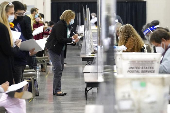 พวกผู้สังเกตการณ์การนับคะแนนใหม่ เฝ้าดูบัตรเลือกตั้ง ระหว่างการดำเนินการนับคะแนนเลือกตั้งใหม่ด้วยมือ  ณ วิสคอนซิน เซนเตอร์ เมืองมิลวอกี รัฐวิสคอนซิน เมื่อวันศุกร์ (20 พ.ย.)  ทั้งนี้มีรายงานว่า เจ้าหน้าที่นับคแนนโวยผู้สังเกตการณ์จากทีมหาเสียงของทรัมป์ พยายามถ่วงเวลาการนับคะแนนใหม่ ด้วยการซักถามและคัดค้านบัตรเลือกตั้งทุกใบ