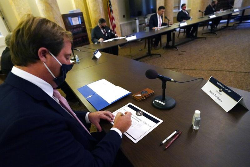 สมาชิกในคณะผู้เลือกตั้งของรัฐมิสซิสซิปปี ลงนามในเอกสารยืนยันการออกเสียง ในพิธีซึ่งจัดขึ้นที่อาคารรัฐสภา เมืองแจ็กสัน วันจันทร์ (14 ธ.ค.)