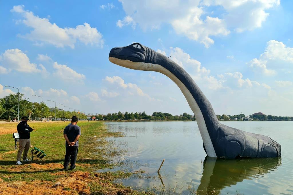 น้องมาเล่นน้ำ! รูปปั้นไดโนเสาร์เกาะกลางถนนมะลิวัลย์ ถูกย้ายมาอยู่ในบึงหนองโคตร จ.ขอนแก่น