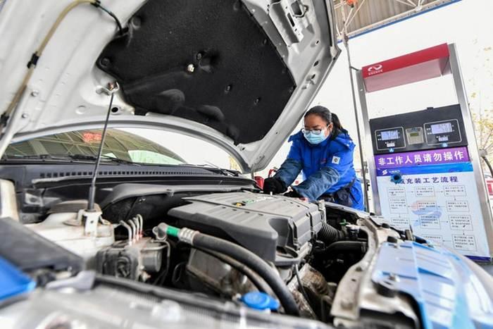 คนงานเติมเชื้อเพลิงรถยนต์ ณ ปั๊มแห่งหนึ่งในเมืองจิ้นเฉิง มณฑลซานซีทางตอนเหนือของจีน วันที่ 9 ธ.ค. 2020--แฟ้มภาพซินหัว