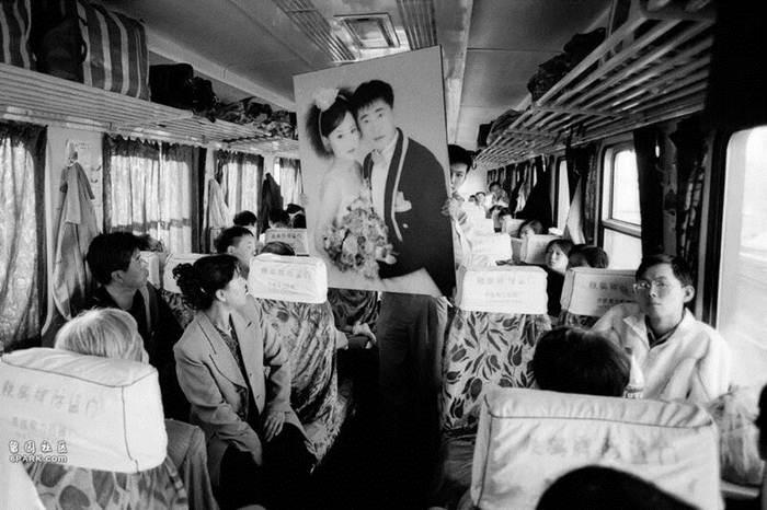 บนขบวนรถไฟฮาร์บิน-จี้จี้ฮาเอ่อร์ ปี 1998 คู่สามี-ภรรยาเพิ่งแต่งงานถือภาพแต่งงานเดินขึ้นขบวนรถไฟ