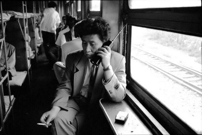 """ผู้โดยสารในขบวนรถไฟสายเมืองเสิ่นหยังและต้าเหลียน กำลังคุยโทรศัพท์มือถือ """"ต้าเกอต้า"""" อย่างเท่ของปี 1994"""