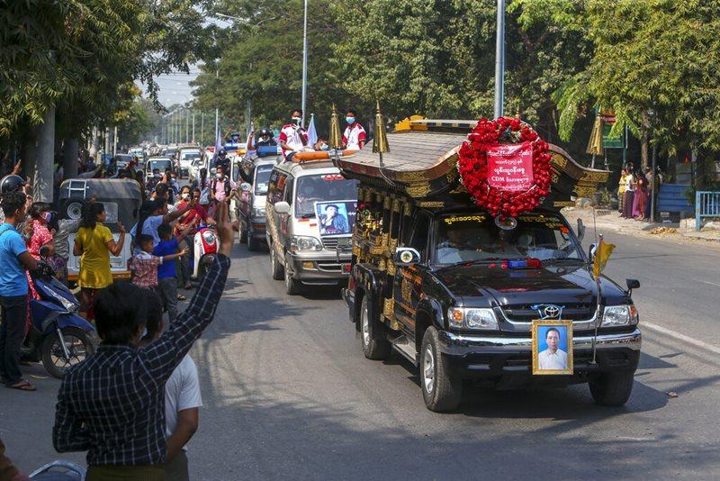 ผู้คนชู 3 นิ้วสัญลักษณ์ของการต่อต้านเผด็จการ ขณะขบวนรถในพิธีศพของ เต๊ต นาย วิน ผู้ประท้วงที่เสียชีวิตจากกระสุนปืนระหว่างเข้าร่วมการชุมนุมต่อต้านทหารก่อรัฐประหารเมื่อสัปดาห์ที่แล้ว แล่นผ่านที่ถนนสายหนึ่งในเมืองมัณฑะเลย์ วันอังคาร (23 ก.พ.)