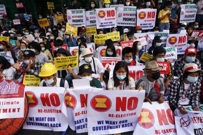ผู้ชุมนุมต่อต้านรัฐประหารชูป้ายประท้วงหน้าสถานทูตอินโดนีเซียในนครย่างกุ้ง.
