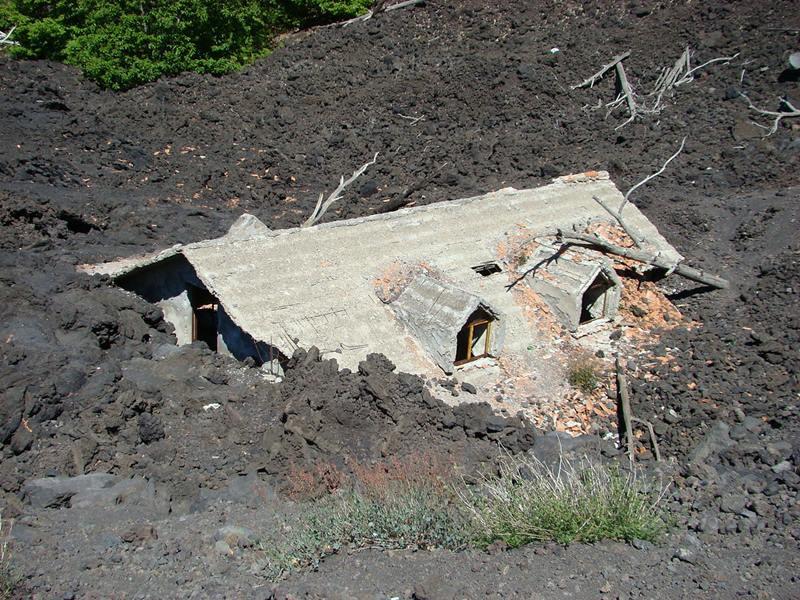 บ้านหลังใหญ่บนเชิงเขาเอตนาถูกสายธารลาวาท่วมทับเกือบมิดหลังคาเมื่อปี 2007 ภาพโดย Hajotthu ช่างภาพเยอรมันซึ่งมอบภาพให้วิกิพีเดียนำไปเผยแพร่