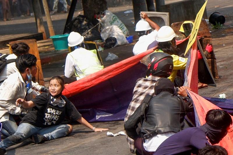 พวกผู้ประท้วงหมอบราบลงกับพื้น หลังตำรวจเปิดฉากยิงใส่เพื่อขับไล่การประท้วงต่อต้านรัฐประหารในเมืองมัณฑะเลย์ เมืองใหญ่อันดับ 2 ของพม่าเมื่อวันพุธ (3 มี.ค.) ในบรรดาผู้ประท้วงเหล่านี้ คนหนึ่งคือนักศึกษามหาวิทยาลัยวัย 20 ปี (ล่างซ้าย) ซึ่งมีชื่อว่า แองเจิล หรือชื่อพม่าคือ จัล ซีน  ชื่อภาษาจีนว่า เติ้ง เจียซี ภาพนี้ถ่ายก่อนเธอจะถูกยิงที่ศีรษะ