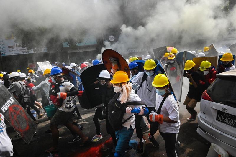 พวกผู้ประท้วงในเมืองย่างกุ้ง เมืองใหญ่ที่สุดของพม่า  พากันถือโล่ทำเองและสวมชุดป้องกันตัวเท่าที่จะหาได้ ขณะออกมาท้าทายตำรวจปราบจลาจล และคอยวิ่งหนีเมื่อถูกยิงด้วยแก๊สน้ำตา เมื่อวันพุธ (3 มี.ค.)
