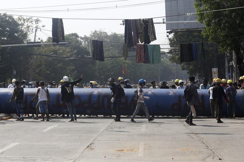 ผู้ประท้วงยืนพักหลังจากช่วยกันกลิ้งท่อขนาดใหญ่มาขวางถนน เพื่อใช้เป็นเครื่องกีดขวาง ขณะเข้าร่วมในการชุมนุมต่อต้านการรัฐประหารยึดอำนาจของฝ่ายทหาร ที่เมืองย่างกุ้ง วันพฤหัสบดี (11 มี.ค.)