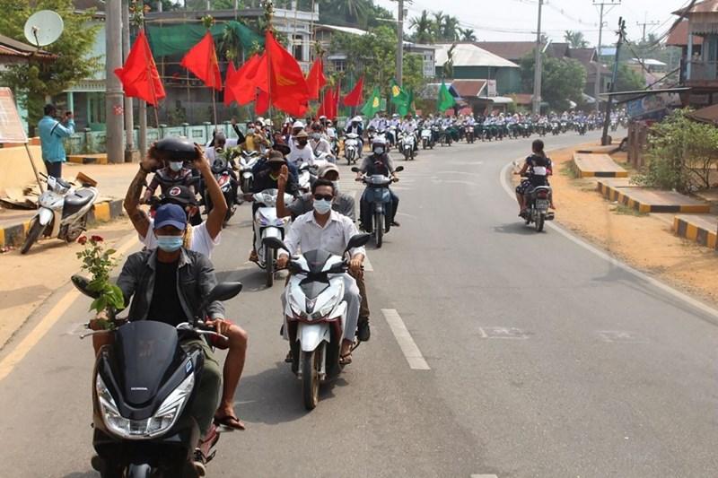 """ประชาชนเข้าร่วมขบวนรถต่อต้านทหารพม่าทำรัฐประหาร ที่เขตลองโลน เมืองทวาย เขตตะนาวศรี ทางด้านตะวันออกเฉียงใต้ของพม่า ทั้งนี้คนที่นั่งซ้อนรถจักรยานยนต์คันหน้าสุดของภาพ ในมือถือภาชนะเหมือนบาตรชูขึ้นเหนือศีรษะ ในลักษณะ """"คว่ำบาตร"""" ซึ่งพบเห็นอยู่บ่อยๆ ในการประท้วงตามท้องที่ต่างๆ ของพม่า (ภาพเผยแพร่เมื่อวันพุธที่ 31 มี.ค. โดยกลุ่มทวาย วอตช์ DAWEI WATCH)"""
