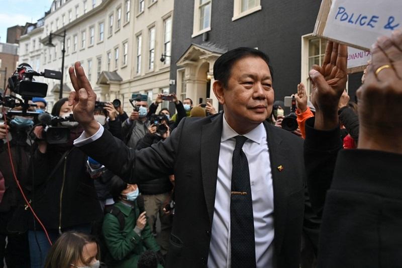 """เอกอัครราชทูต จ่อ ซามิน ชูสามนิ้วสัญลักษณ์ต่อต้านเผด็จการ ขณะกลับมาที่ด้านนอกของสถานเอกอัครราชทูตพม่าประจำสหราชอาณาจักร ในกรุงลอนดอน ท่ามกลางสื่อมวลชนและผู้มาประท้วงทหารพม่ายึดอำนาจ  เมื่อวันพฤหัสบดี (8 เม.ย.) หลังจากถูกเจ้าหน้าที่ในสถานทูตซึ่งภักดีต่อคณะปกครองทหาร """"ทำรัฐประหาร"""" ปิดประตูไม่ยอมให้เขากลับเข้าไป"""