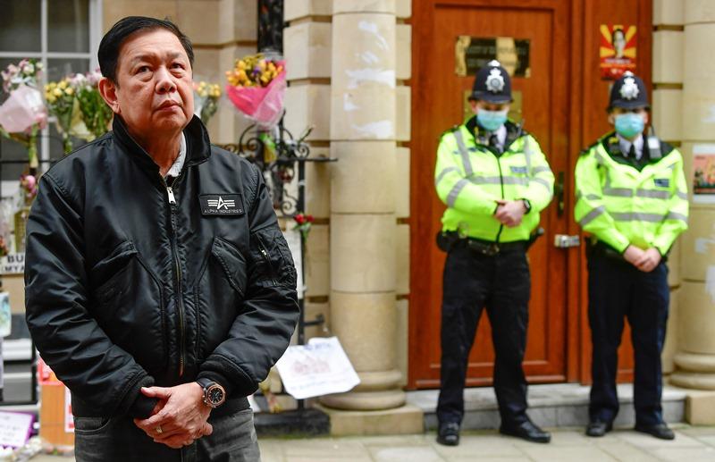 """เอกอัครราชทูต จ่อ ซามิน  ยืนอยู่ด้านนอกของสถานเอกอัครราชทูตพม่าประจำกรุงลอนดอน หลังจากถูกเจ้าหน้าที่ในสถานทูตซึ่งภักดีต่อคณะปกครองทหาร """"ทำรัฐประหาร"""" ปิดประตูไม่ยอมให้เขากลับเข้าไป"""