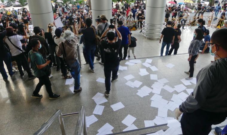 ภาพ ที่ศาลอาญา แกนนำแนวร่วมธรรมศาสตร์ฯ โปรยเอกสารรายชื่อที่รวบรวมมาทั้งหมดรอบบันไดศาล ขอบคุณภาพจากไทยโพสต์