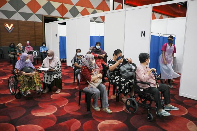 ประชาชนรอรับการฉีดวัคซีนป้องกันโรคโควิด-19 ที่ศูนย์ฉีดวัคซีนแห่งหนึ่งในเมืองสุบังจายา, มาเลเซีย เมื่อวันที่ 26 เม.ย.