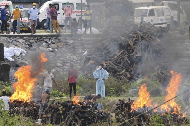 เผาศพผู้เสียชีวิตด้วยโรคโควิด-19 ที่เมรุชั่วคราว ในสถานเผาศพ ซึ่งตั้งอยู่นอกเมืองสิลิกูริ รัฐเบงกอลตะวันตก ประเทศอินเดีย เมื่อวันอังคาร (4 พ.ค.)