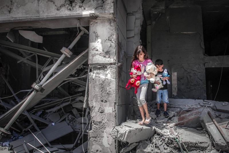 เด็กๆ ชาวปาเลสไตน์ เข้าไปเก็บของเล่นออกมาจากที่พักของพวกเขา ซึ่งอยู่ที่อาคาร อัล-จาวารา ทาวเวอร์ ในเมืองกาซาซิตี้ วันจันทร์ (17 พ.ค.)  โดยที่อาคารหลังนี้ถูกอิสราเอลถล่มทิ้งระเบิดพังยับเยิน