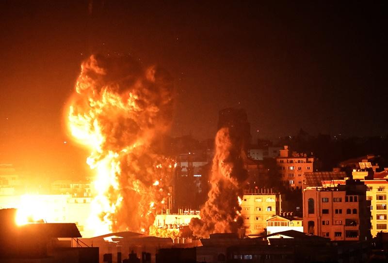 พระเพลิงและกลุ่มควันหนาลอยขึ้นเหนืออาคารหลายหลังในนครกาซาซิตี้ ขณะฝูงเครื่องบินอิสราเอลเข้าถล่มโจมตีเป้าหมายในดินแดนฉนวนกาซาตอนช่วงก่อนรุ่งสางวันจันทร์ (17 พ.ค.)