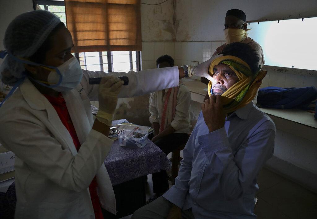 หมอชาวอินเดียผู้หนึ่งตรวจเช็กคนไข้ที่ฟื้นตัวจากโรคโควิด-19 แล้ว แต่เวลานี้มีอาการติดเชื้อราสีดำ  ณ โรงพยาบาลรัฐบาลแห่งหนึ่งในมืองไฮเดอราบัด วันพฤหัสบดี (20 พ.ค.)