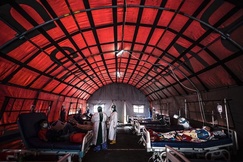 บุคลากรทางการแพทย์ดูแลผู้ป่วยโรคโควิด-19 ภายในเต็นท์ซึ่งตั้งขึ้นที่ด้านนอกของโรงพยาบาลแห่งหนึ่งในเมืองโบกอร์ ประเทศอินโดนีเซีย ในวันอังคาร (29 มิ.ย.) ขณะที่จำนวนผู้ติดเชื้อกำลังเพิ่มสูงขึ้นอย่างรวดเร็ว