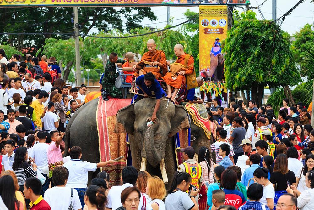 ประเพณีแห่เทียนพรรษาและตักบาตรบนหลังช้าง (ภาพจาก Facebook : ททท.สำนักงานสุรินทร์)