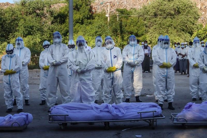 (ภาพจากแฟ้มถ่ายเมื่อ 14 ก.ค. 2021) บรรดาอาสาสมัครสวมชุดป้องกันส่วนบุคคล ทำพิธีสวดที่ด้านหน้าของศพผู้เสียชีวิตจากโควิด-19 ก่อนฝังศพ ณ สุสานแห่งหนึ่งในเมืองมัณฑะเลย์ เมืองใหญ่อันดับ 2 ของพม่า
