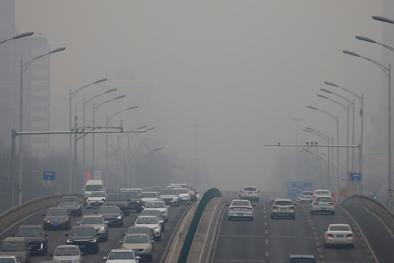 รถยนต์แล่นไปตามถนนในกรุงปักกิ่ง เมื่อวันที่ 13 กุมภาพันธ์ 2021 ซึ่งเป็นวันหนึ่งที่อากาศในเมืองหลวงของจีนเลวร้ายสุดๆ