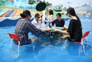 ชาวจีนคลายร้อน จุ่มเท้าแช่น้ำเล่นไพ่นกกระจอกกลางสระน้ำ (ชมภาพ)