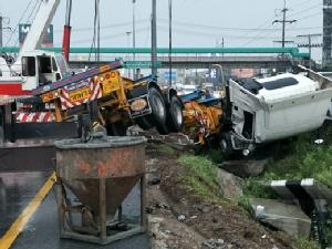 ฝนตกหนักถนนลื่นพ่วงเทรลเลอร์พลิกคว่ำใกล้โรงงานกูลิโกะ ทำรถติดยาวบนถนนพหลโยธิน