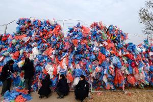 อาสาสมัครช่วยกันนำถุงพลาสติกที่เก็บมาจากแหล่งสาธารณะ มาสร้างเป็นแผนที่ทะเลเดดซี เพื่อส่งข้อความไปถึงชาวโลกให้ช่วยกันลดขยะพลาสติก ก่อนที่ทะเลทั้งหลายจะกลายเป็นทะเลมรณะจากขยะเหล่านี้ (PRAKASH MATHEMA / AFP)