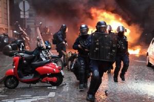 <i>ตำรวจปราบจลาจลวิ่งอยู่ใกล้ๆ รถยนต์คันหนึ่งซึ่งถูกเผา ระหว่างการประท้วงของกลุ่มเสื้อกั๊กเหลือง บนถนนช็องเอลิเซ ในกรุงปารีส วันเสาร์ (8 ธ.ค.) </i>