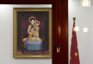 """ธงประจำชาติจีนเคียงคู่ภาพเขียน """"พระนางมารีย์พรหมจารีและพระกุมารเยซู"""" สวมชุดเครื่องแต่งกายแบบสมัยราชวงศ์ชิงภายในอาสนวิหารซีสือ คาธีดรัล หรือที่รู้จักกันในชื่อ North Cathedral กรุงปักกิ่งในวันคริสต์มาส อีฟ 24 ธ.ค. (ภาพ รอยเตอร์ส)"""
