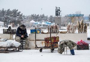 ชายขายปลาในตลาดเกษตรที่เมืองยาคุตสค์ท่ามกลางอุณหภูมิ -35 องศาเซลเซียส (Mladen ANTONOV / AFP)