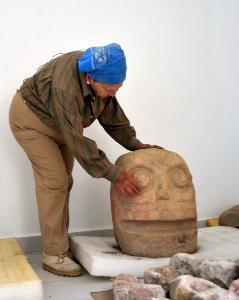 โนเอมิ กัสติโย เตเฆโร และรูปปั้นศรีษะเทพ ซิเป โทเทก (Meliton TAPIA / INAH / AFP)