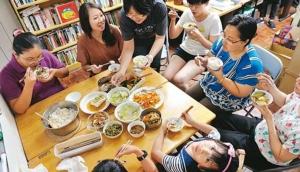 พนักงานบริษัทหนึ่งต่างคนต่างเอาอาหารจากบ้านมาแบ่งกันกิน ขอบคุณภาพจาก http://www.commonhealth.com.tw/article/article.action?nid=75443