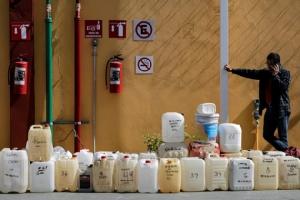 ชายชาวเม็กซิกันรายหนึ่งกำลังคุยโทรศัพท์มือถือใกล้กับถังแกลลอนสำหรับบรรจุน้ำมันที่ชาวบ้านพากันมาตั้งรอเพื่อเป็นแถวต่อคิวซื้อน้ำมันเชื้อเพลิงเพื่อเติมรถที่ปั้มน้ำมันแห่งหนึ่งในโมเรเลีย ( Morelia) เม็กซิโก วันพุธ(9 ม.ค) ภาพรอยเตอร์