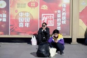 """กลุ่มผู้โดยสารนั่งพักที่บริเวณหน้าสถานีรถไฟในปักกิ่ง ภาพ วันที่ 21 ม.ค. 2019 วันแรกของการเดินทาง """"ชุนอวิ้น"""" หรือการเดินทางช่วงเทศกาลตรุษจีน (ภาพ รอยเตอร์ส)"""